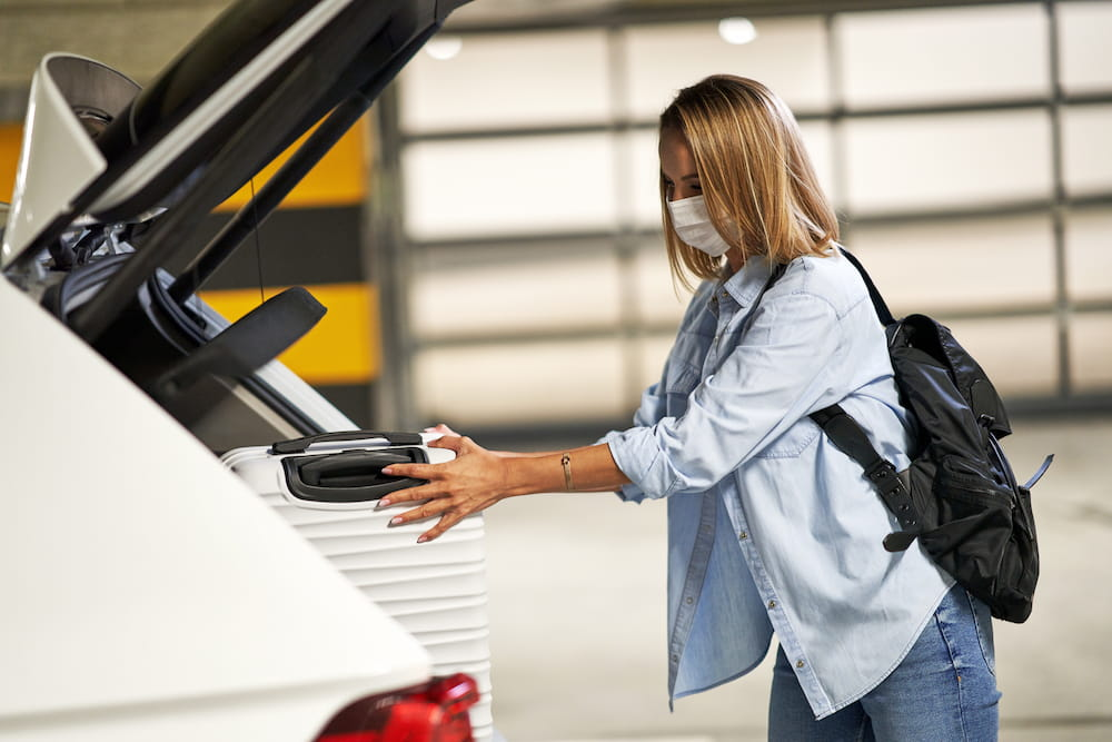 Woman wearing mask putting suitcase in car