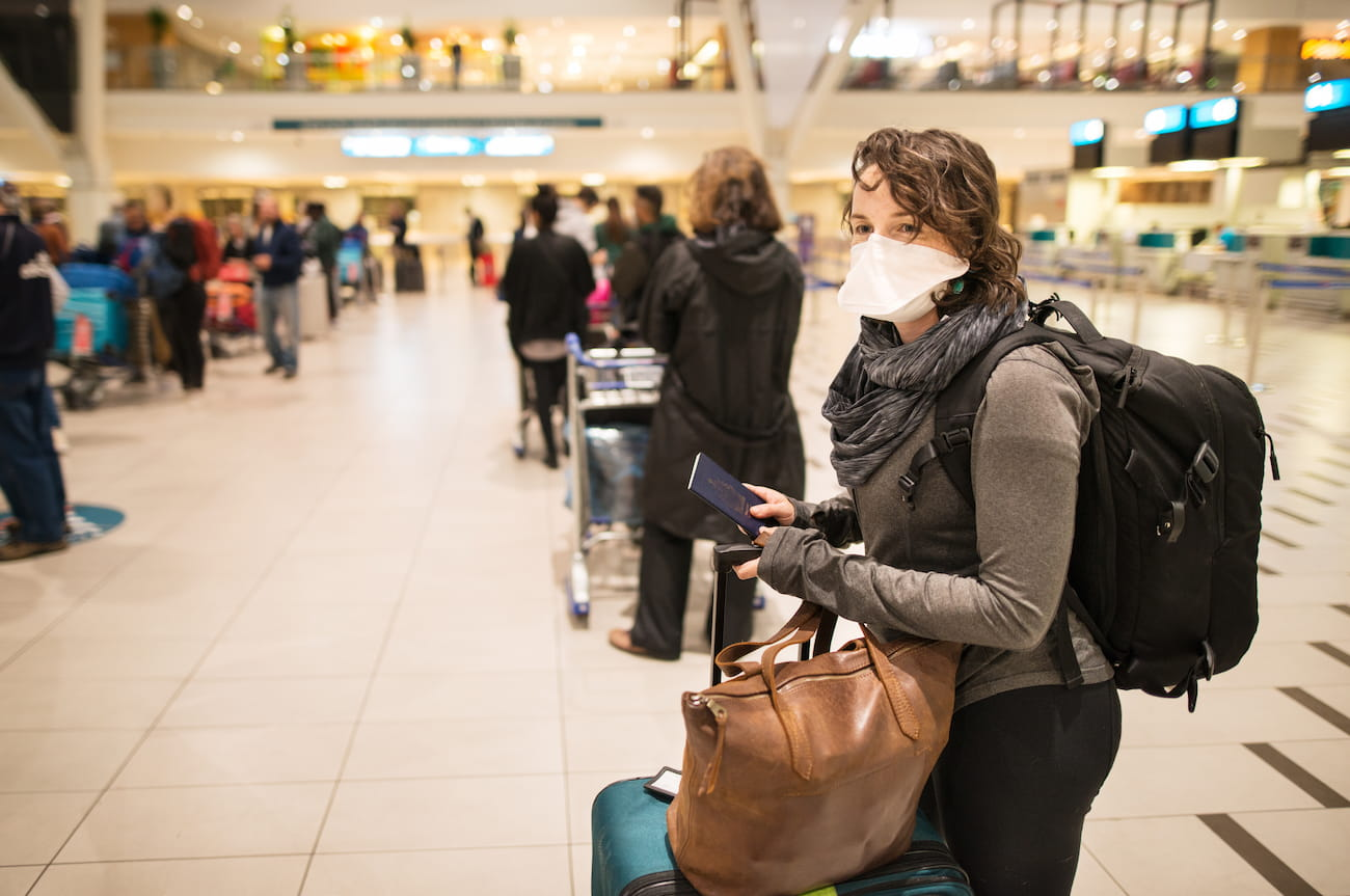 person with mask in airport queue