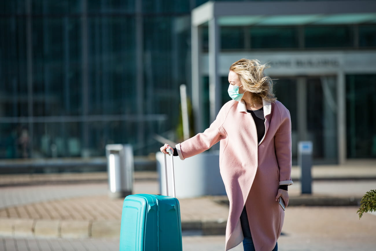 Woman outside airport wearing mask with suitcase