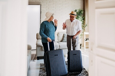 Elderly couple with suitcases