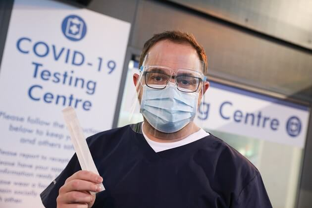 person wearing PPE holding COVID-19 test at airport testing centre