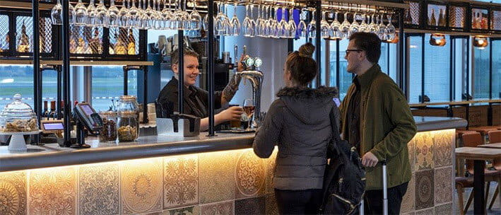 Customers stood at the bar in the Nook at Manchester Airport