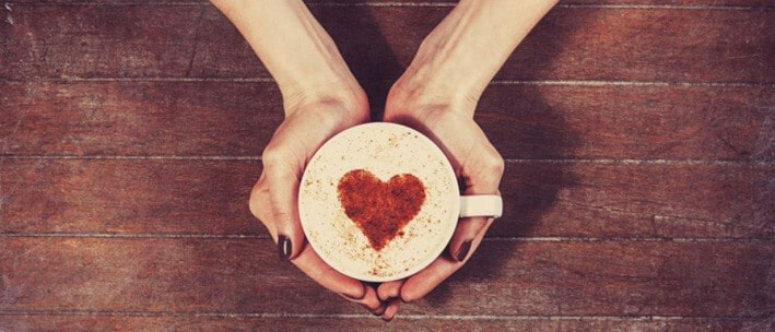 Person holiday cup of coffee with heart shape in chocolate in the froth