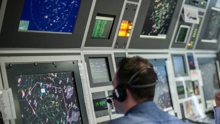 Man looking at airspace computer screens