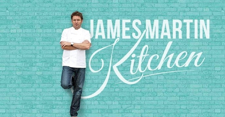 James Martin leaning against a wall with James Martin Kitchen logo behind