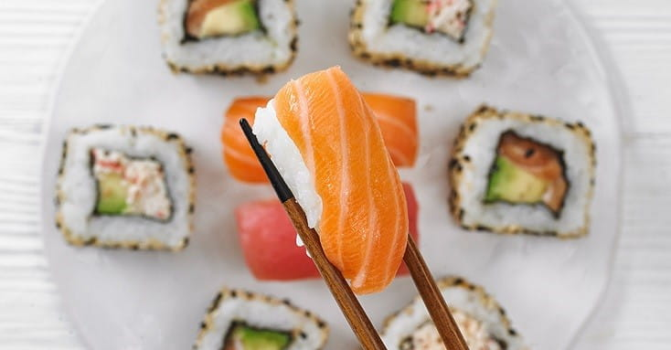 Sushi held with chop sticks over a plate
