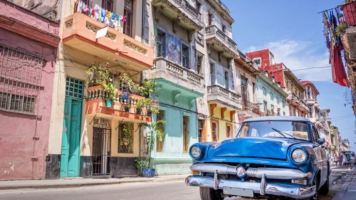 a vintage car parked in front of colourful buildings in Cuba